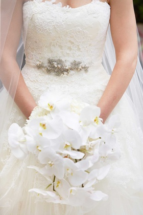 bride holds cascading bouquet of white orchids in her white bridal ball gown vera wang