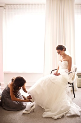 Bride in strapless Monique Lhuillier gown having bridesmaid help put on white wedding shoes