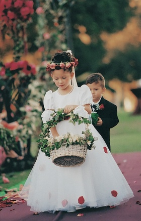 White flower girl dress and basket of rose petals