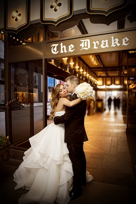 groom in tuxedo kisses bride in alyne ball gown on the cheek in front of the drake hotel