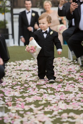 Ring bearer in tuxedo carrying corner of pillow with flowers on top