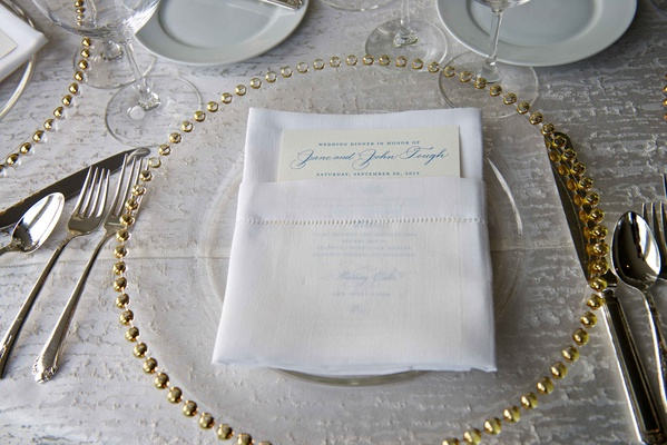 Wedding reception place setting with clear glass gold beaded charger, menu with blue print in napkin