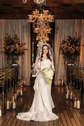 bride in oscar de la renta lace sheath gown with ruffled organza train