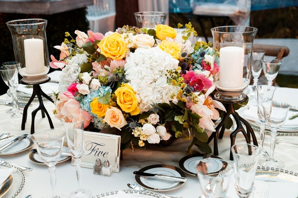 Low centerpiece with yellow rose, blue hydrangea, white flowers, pink flowers thistle unique candles