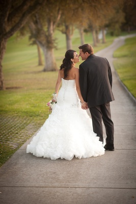 Bride in a Maggie Sottero dress with ruffled skirt holds hands with groom in black tuxedo