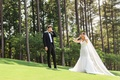 Bride covering her eyes on grass lawn before first look with groom in forest groom covering eyes too