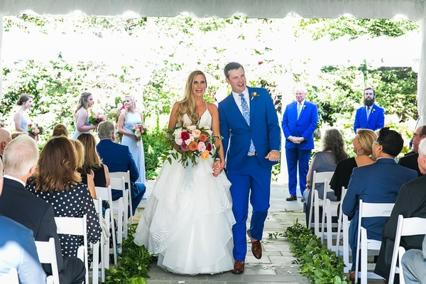 bride and groom recessional outdoor wedding stone aisle greenery blue suit pink bouquet