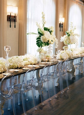 Long head table with wood top, high and low tropical centerpieces, Ghost chairs