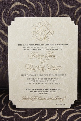 tan wedding invitation with lace background and gold monogram and print