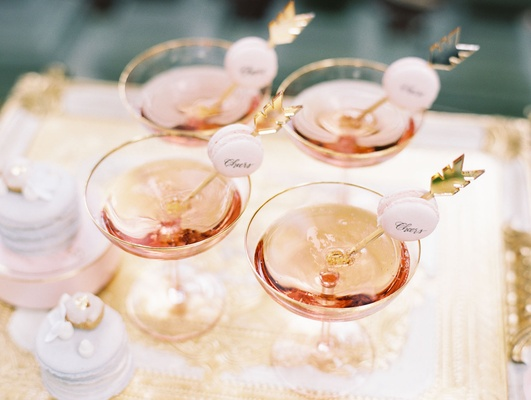 Wedding cocktail hour gold bar cart coupe glass with rose champagne and cheers macaron on arrow