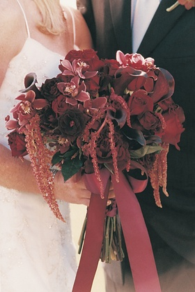 Burgundy flowers tied together with rouge ribbon