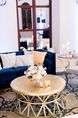 wedding reception ballroom navy blue velvet tufted sofa white pom tassel pillows gold coffee table