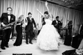 black and white photo of bride in vera wang ball gown dancing on stage with live band
