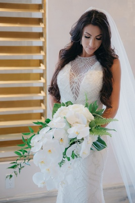 bridal bouquet with white Phalaenopsis orchids, ferns, tropical leaves, greenery