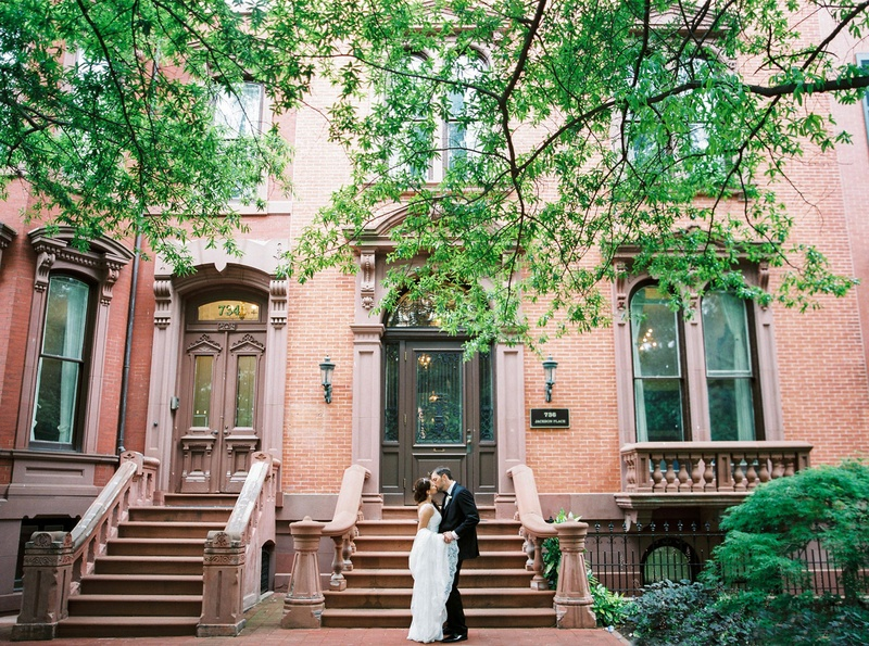 Bride in wedding dress from The White Dress kissing groom in front of brownstone building DC
