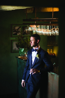 groom in navy armani suit and matching bow tie leans against bar