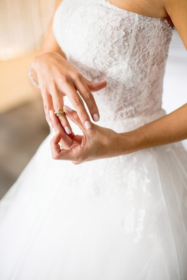 bride in monique lhuillier ball gown puts on heirloom diamond ring from grandmother