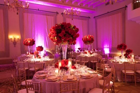 Round tables with red floral centerpieces