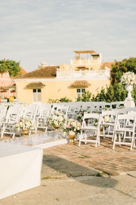 colombia wedding ceremony raised aisle white chairs low flowers gold urns