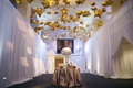 Gold star shaped balloons on ceiling at cocktail hour for New Year's Eve wedding above table drapery