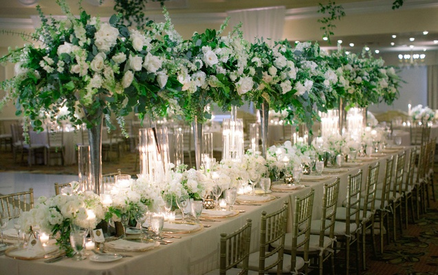 wedding reception head table with tall centerpieces heavy greenery white flowers