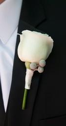 Groom wearing single flower on tuxedo lapel
