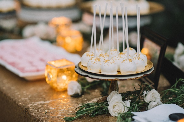 Gold sprinkle dusted white cake pops and pink macaron desserts