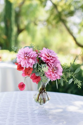 a small floral arrangement of flowers in different shades of pink and foliage in small vase