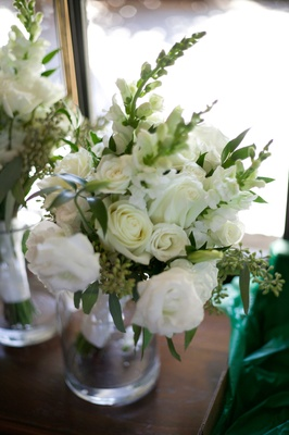 bridesmaid bouquet with white flowers roses and green leaves foliage in glass vase