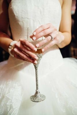 Bride with engagement ring and pearl bracelet holding sparkling crystal champagne flute