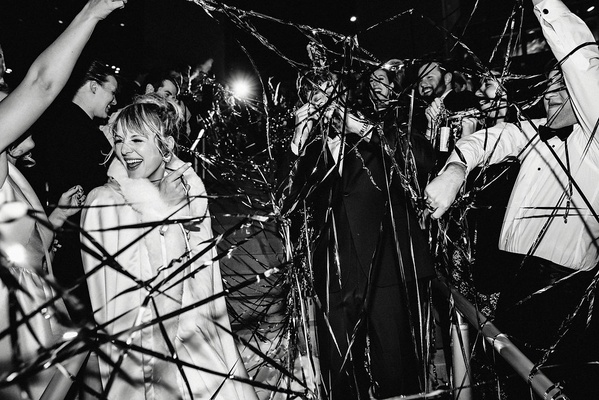 black and white photo of bride and groom leaving wedding, metallic streamers