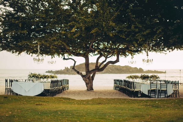 outdoor reception beach chandeliers trees white long table punta mita mexico destination wedding