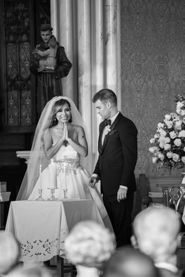 black and white photo of bride in alyne ball gown and groom in tuxedo with unity candle