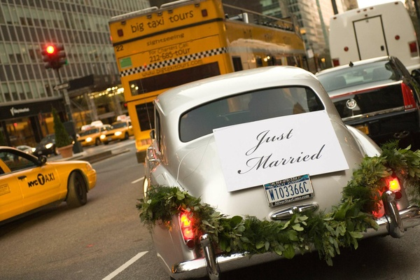 Wedding car with Just Married sign and leaf garland