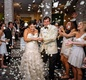Guests toss white rose petals at bride and groom
