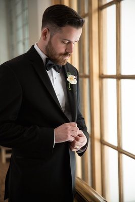 Groom looking down at window sill in black tuxedo and bow tie