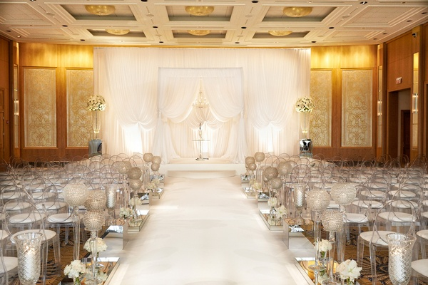 All White Wedding Ceremony With Drapery Arches And Clear Ghost Chairs Cushions