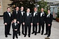 groom and ring bearer and groomsmen in black tuxedos stand in chicago