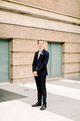 groom in navy suit and black dress shoes waiting for bride before first look