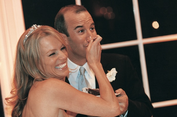 Bride and groom share piece of wedding cake, bride's headpiece