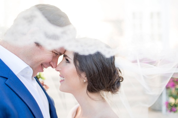 Bride smiles into groom's eyes The Confused Millennial at wedding shoot veil lace trim