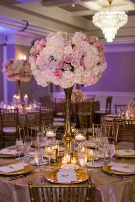 blush and ivory floral centerpiece on gold stand, purple uplighting ballroom reception