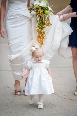 Flower girl in white dress and bow walking in front of bride