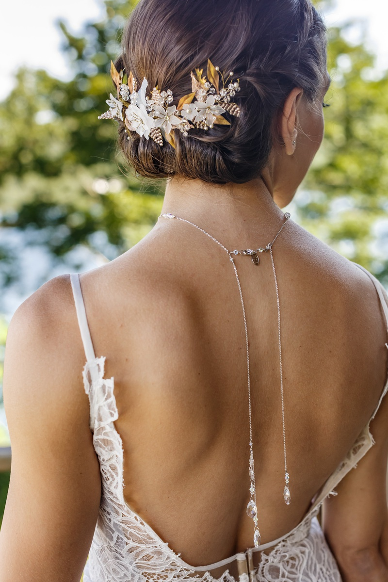 bridal headpiece with gold leaves and white flowers on bridal updo, back necklace