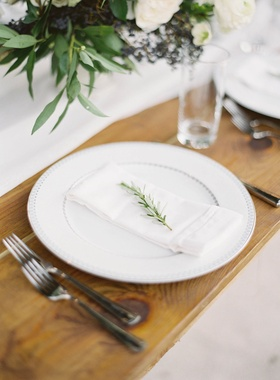 White china plate on wood table sprig of fresh rosemary on napkin on plate silver flatware