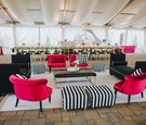 wedding lounge area, black couches, bright pink couches, black-and-white striped ottomans
