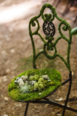 Bistro chair covered with moss at forest wedding ceremony