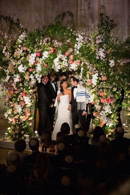 Bride and groom in tallit under floral chuppah