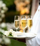 Champagne in flutes with white roses on tray
