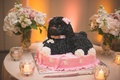 Groom's cake in the shape of a black dog with pink bows on a pink dog bed with white paw prints